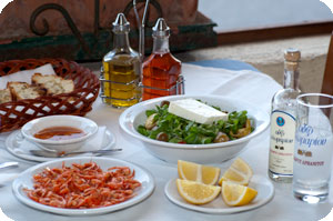 Typical Greek food table, some fish, salad, bread and ouzo!